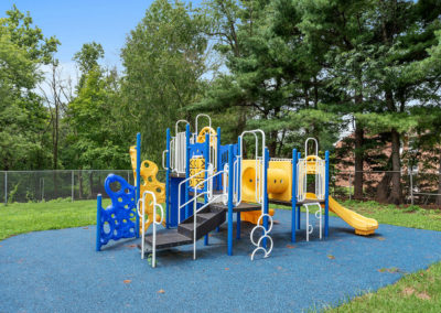 Playground with a blue and yellow jungle gym at Creekside Apartments