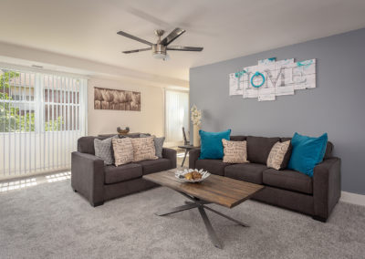 Living room with carpet flooring, grey couches, coffee table, and large windows