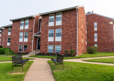 Exterior of Creekside Apartments in Bensalem with two benches