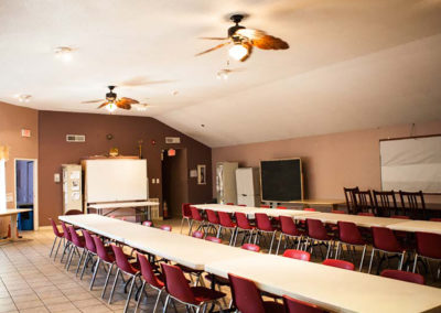 Creekside Apartments community room with two long tables with chairs around them.