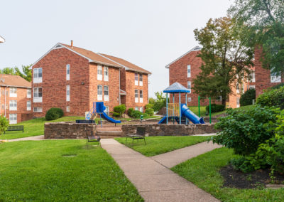 Creekside Apartments exterior with red brick buildings and a blue jungle gym