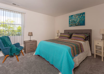 Furnished bedroom with a queen bed, teal accent chair, carpet flooring, and large windows with blinds