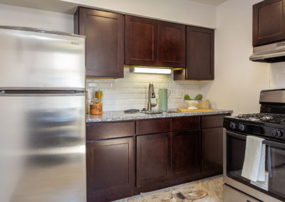 Kitchen area Creekside apartments with brown cabinets and stainless-steel appliances