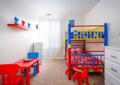 Children's bedroom with a multi colored bunk beds, carpet flooring, and white dressers